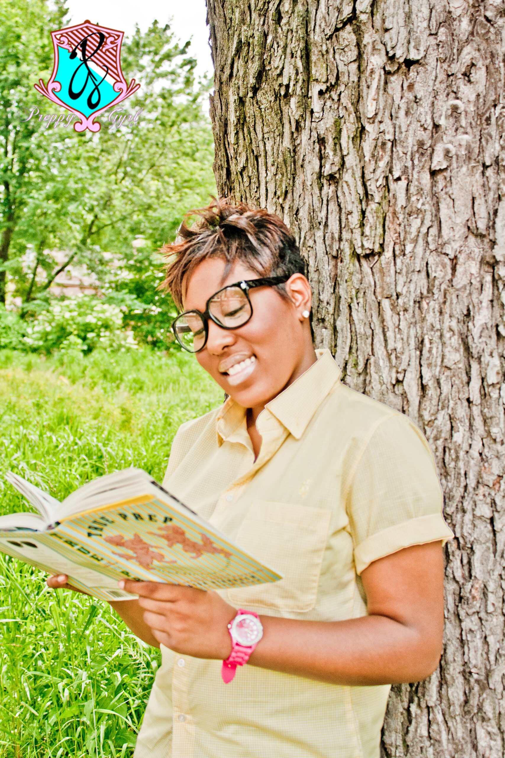 girl with glasses and yellow shirt standing agent a tree. reading a book, the preppy girl. logo hovers above her head